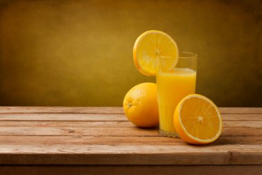 Fresh orange juice on wooden table over grunge background stock vector