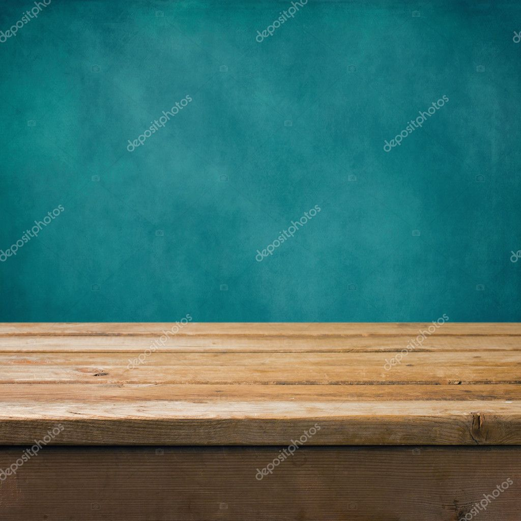 Background with wooden table and grunge blue wall
