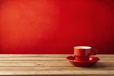 Red coffee cup on wooden table over red grunge background
