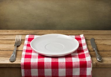 Empty plate on wooden table over grunge background