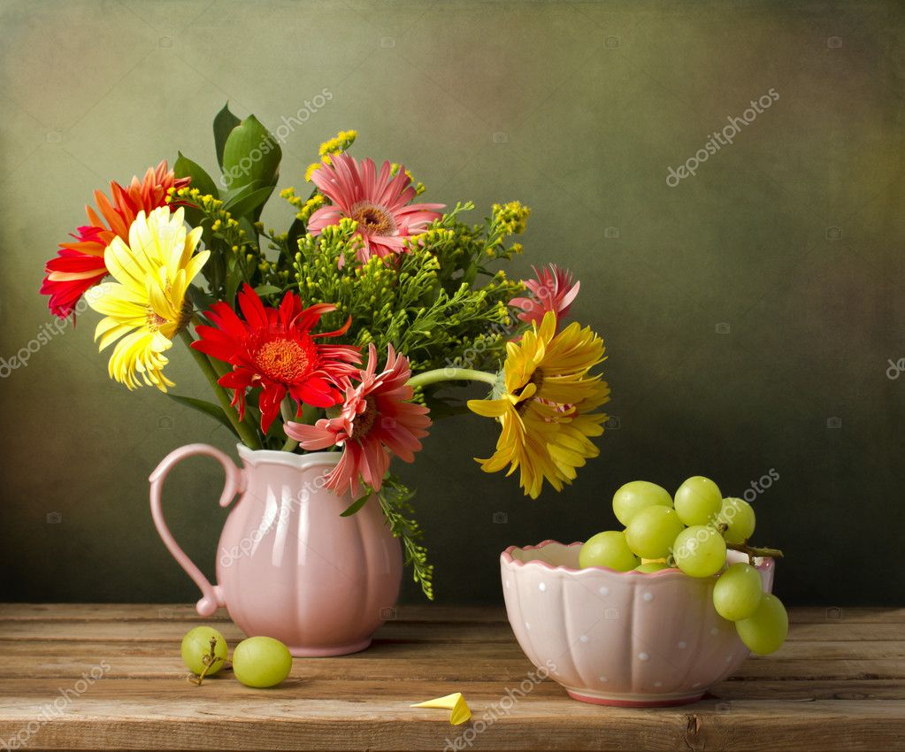 Still life with beautiful flower bouquet and green grapes