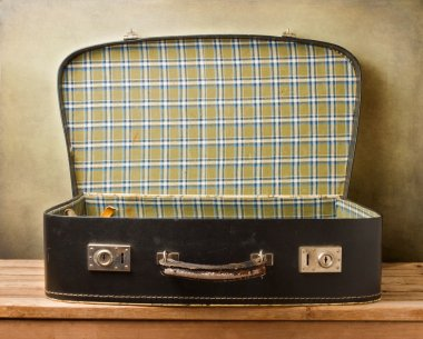 Empty vintage open suitcase on wooden table