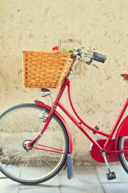 Vintage bicycle with basket over concrete wall
