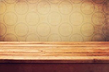 Empty wooden deck table over grunge retro wallpaper