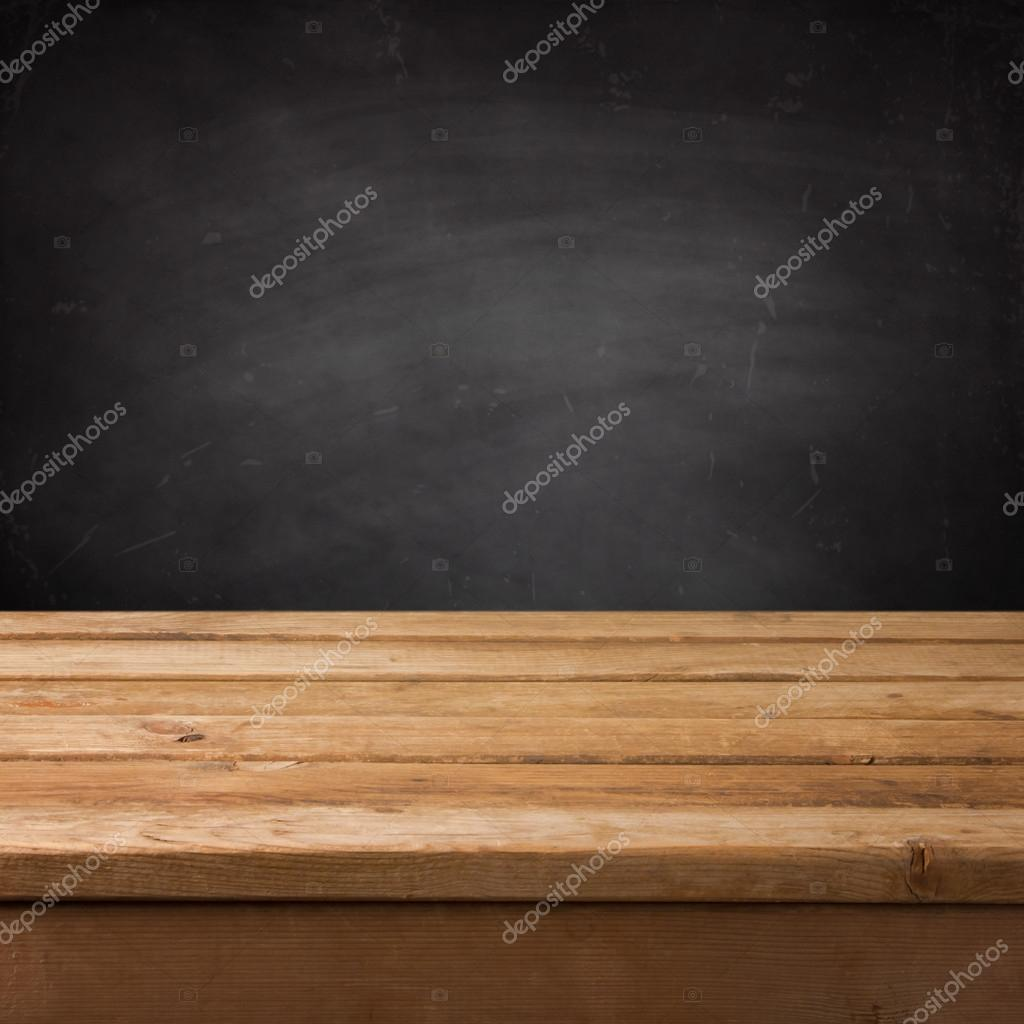 Empty wooden deck table over chalkboard