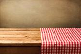 Fotografie prázdné dřevěný stůl pokrytý červenými zaškrtnutých ubrus