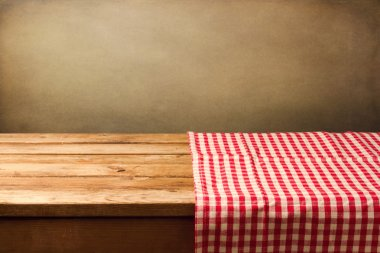 Empty wooden table covered with red checked tablecloth