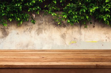 Wooden deck table over urban wall with leaves