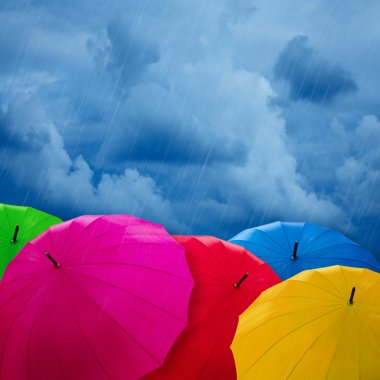 Colorful umbrellas over cloudy sky