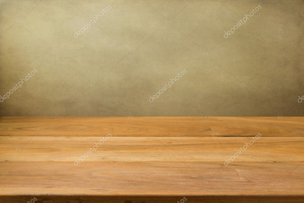 Empty wooden table over grunge background.