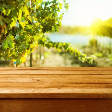 Empty wooden deck table over vineyard bokeh background