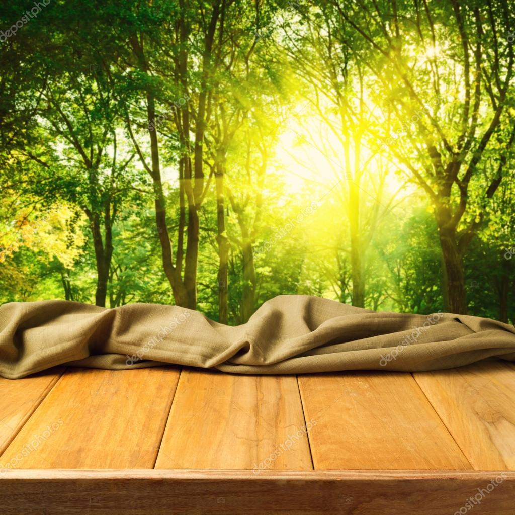 Empty wooden deck table with fabric cloth over forest background