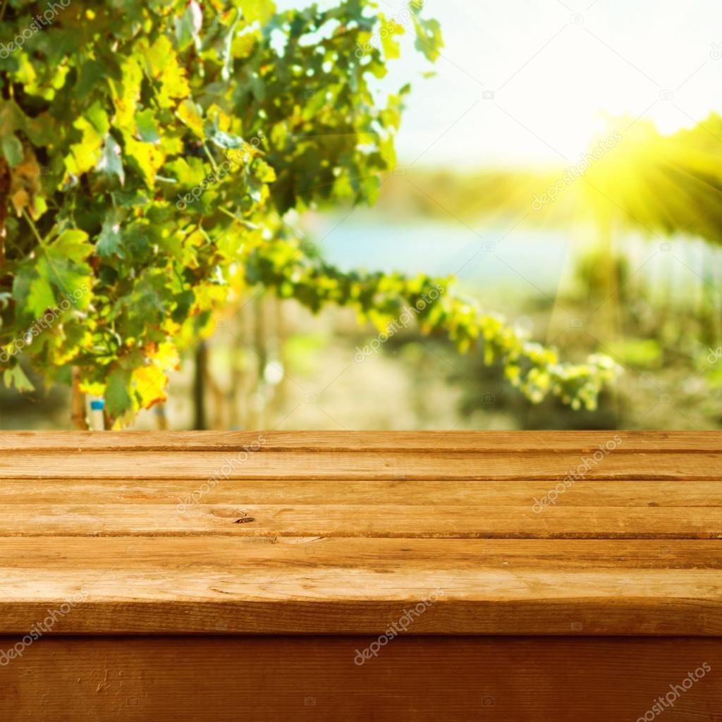 Empty wooden deck table over vineyard bokeh background