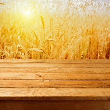 Empty wooden deck table over wheat field with sunset or sunrise.