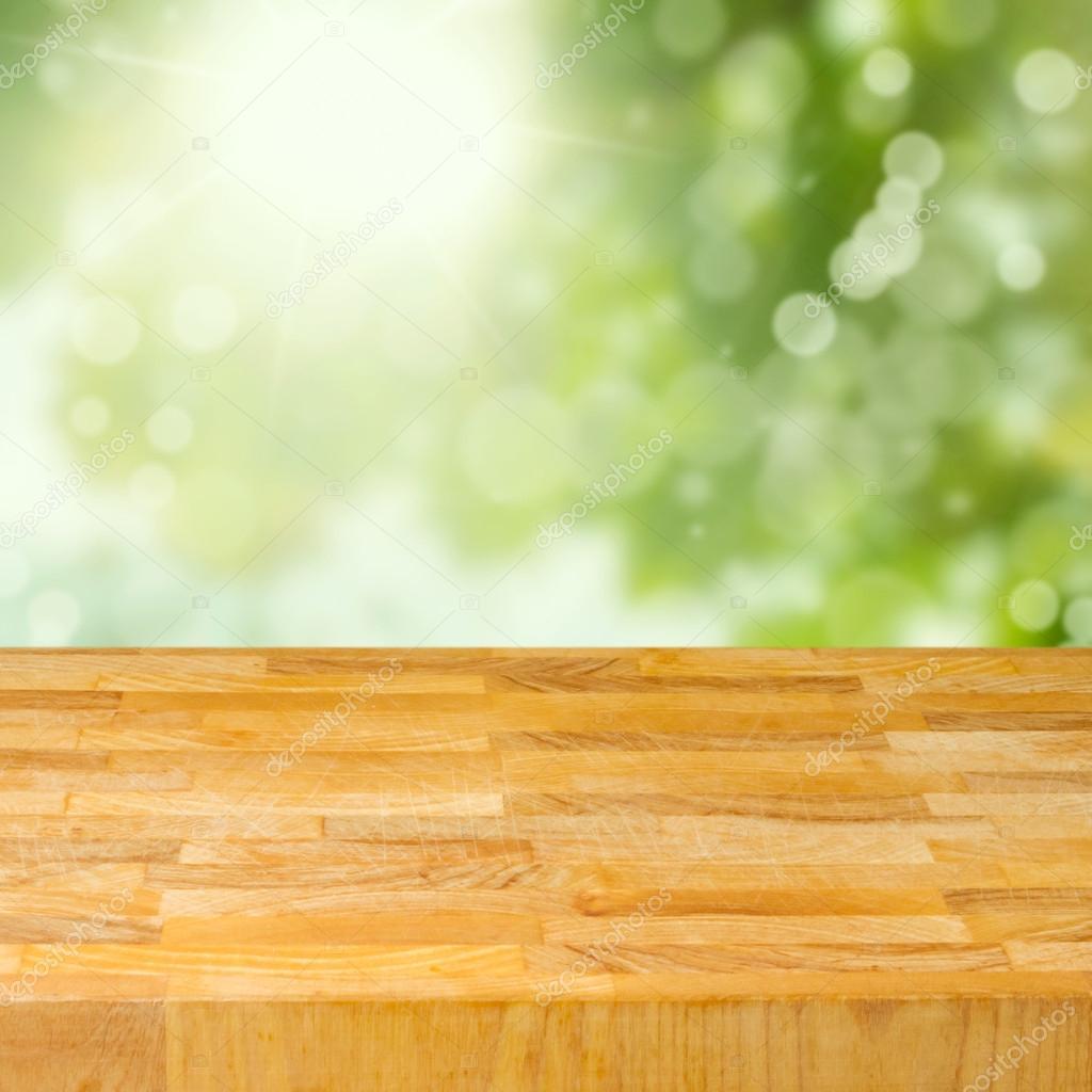 Empty wooden table over garden bokeh background.