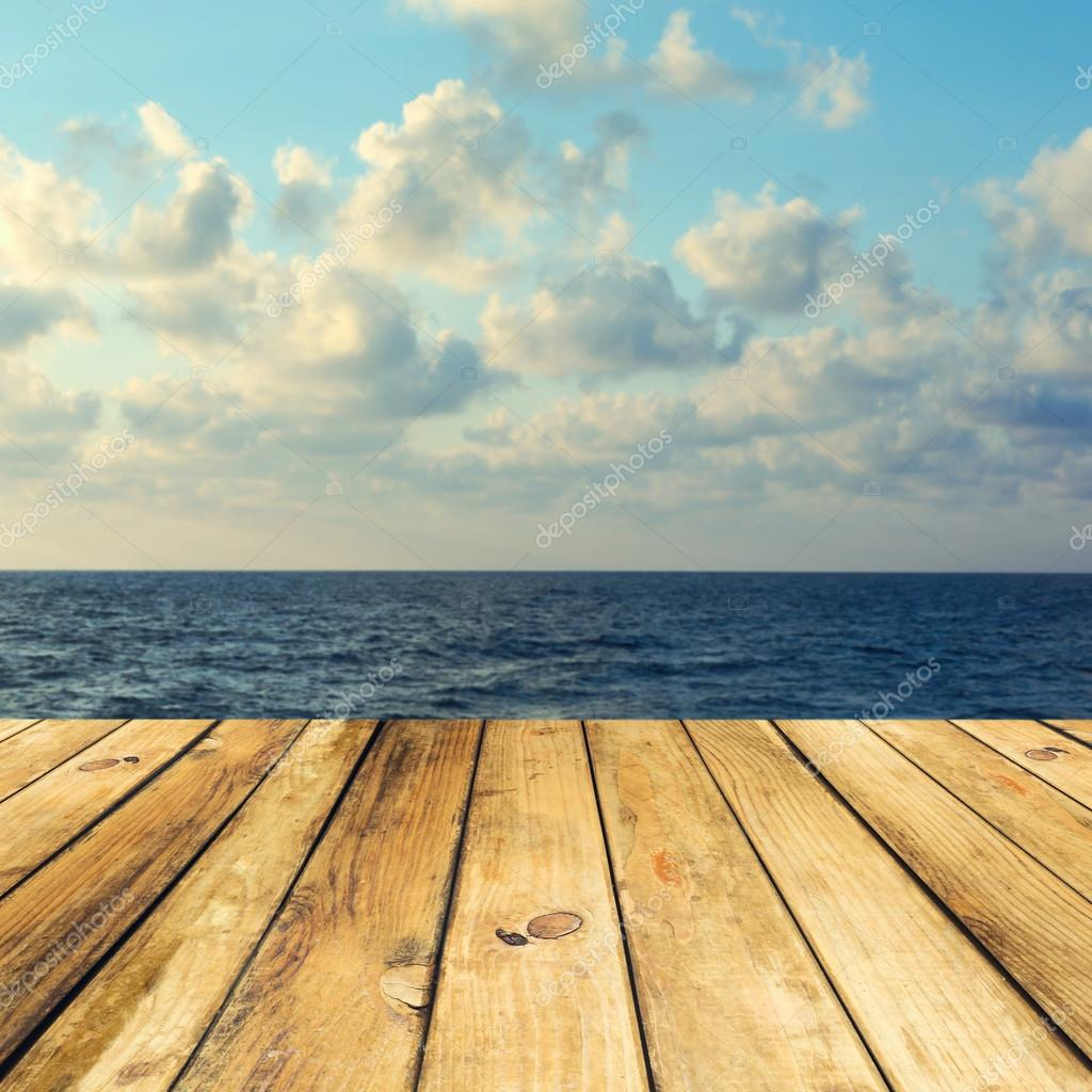 Wooden deck floor over beautiful sea and sky background