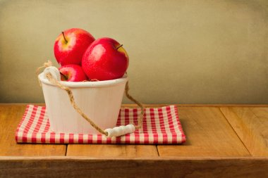 Apples in wooden bucket on tablecloth