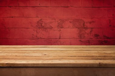 Wooden deck table over grunge brick wall.