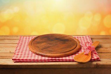 Round board on tablecloth on table
