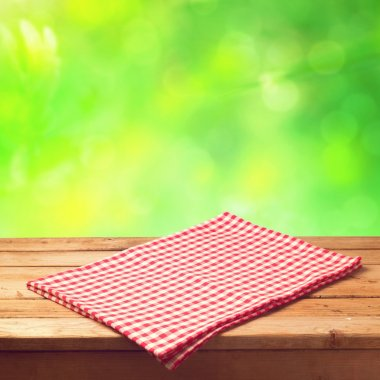 Wooden table with tablecloth over bokeh background
