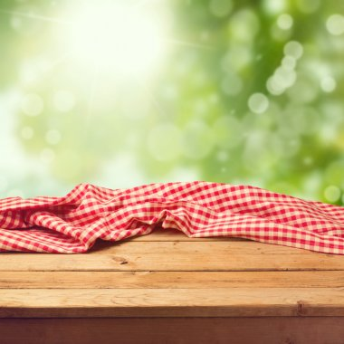 Empty wooden deck table with tablecloth over green bokeh background stock vector