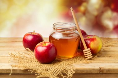 Apples with honey jar on wooden table
