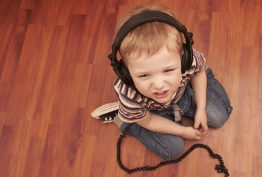 Funny child listening music in headphones
