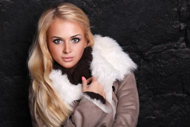 Beautiful blond woman in a fur near bricks wall.winter style. long hair.fur coats and fur store