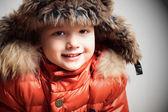 Fotografie Smiling child in fur hood and orange winter jacket. fashionable boy