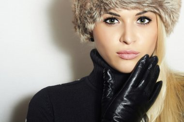 Beauty Fashion Blond Young Woman in Fur Hat. Beautiful Blond Girl in Black Leather Gloves. Winter Fashion