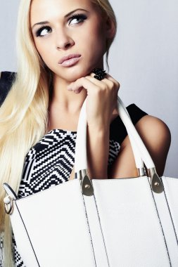 Fashion beautiful blond woman with handbag.