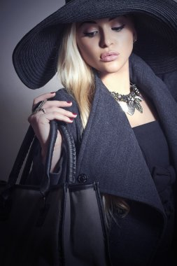 Beautiful Blond Woman in Black Hat. Fashionable Lady in Topcoat. Elegance Beauty Girl with Handbag. Spring Shopping
