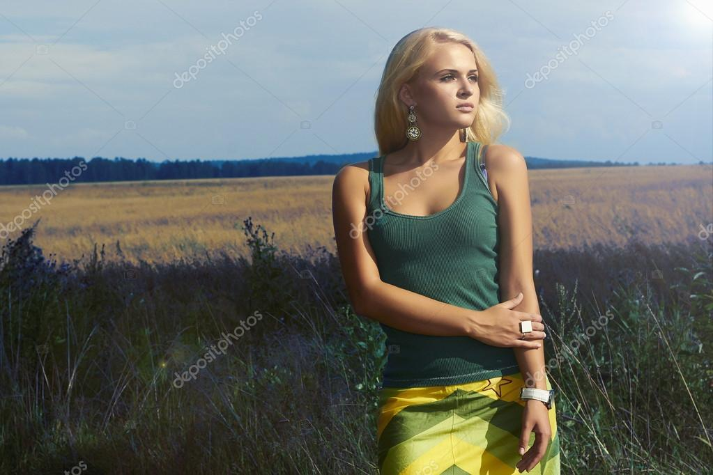 Beautiful model posing on the field.Blond Woman.nature background.Summer Sun.Flowers