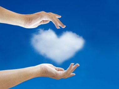 hand and heart cloud shape with blue sky