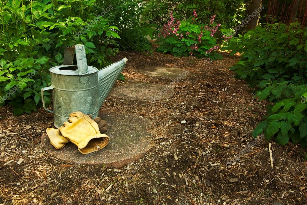An old watering can and gloves sit on a Garden Path in the Woods