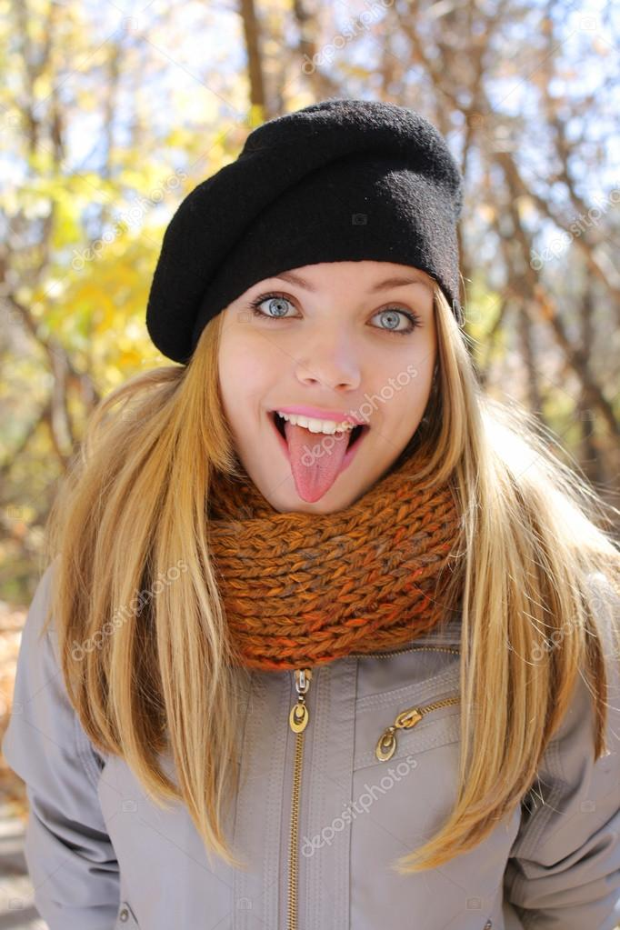 Funny blonde girl shows tongue
