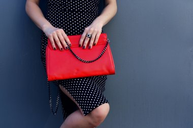 Fashion stylish young woman with red clutch in hand