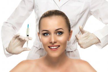 Cosmetic injection to the pretty Beautiful woman face and beautician hands with syringe. Doctor woman giving botox injections.