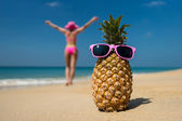 Fotografie Cheerful pineapple glasses and a woman in a bikini sunbathing on the beach on sea background. Idealistic scene leisure travel.