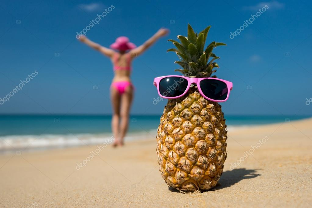 Cheerful pineapple glasses and a woman in a bikini sunbathing on the beach on sea background. Idealistic scene leisure travel.