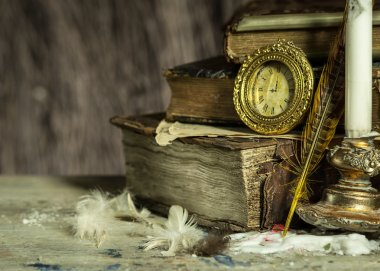 Old books, antique clock, candle in a candlestick and quill on wooden background. Vintage postcard.