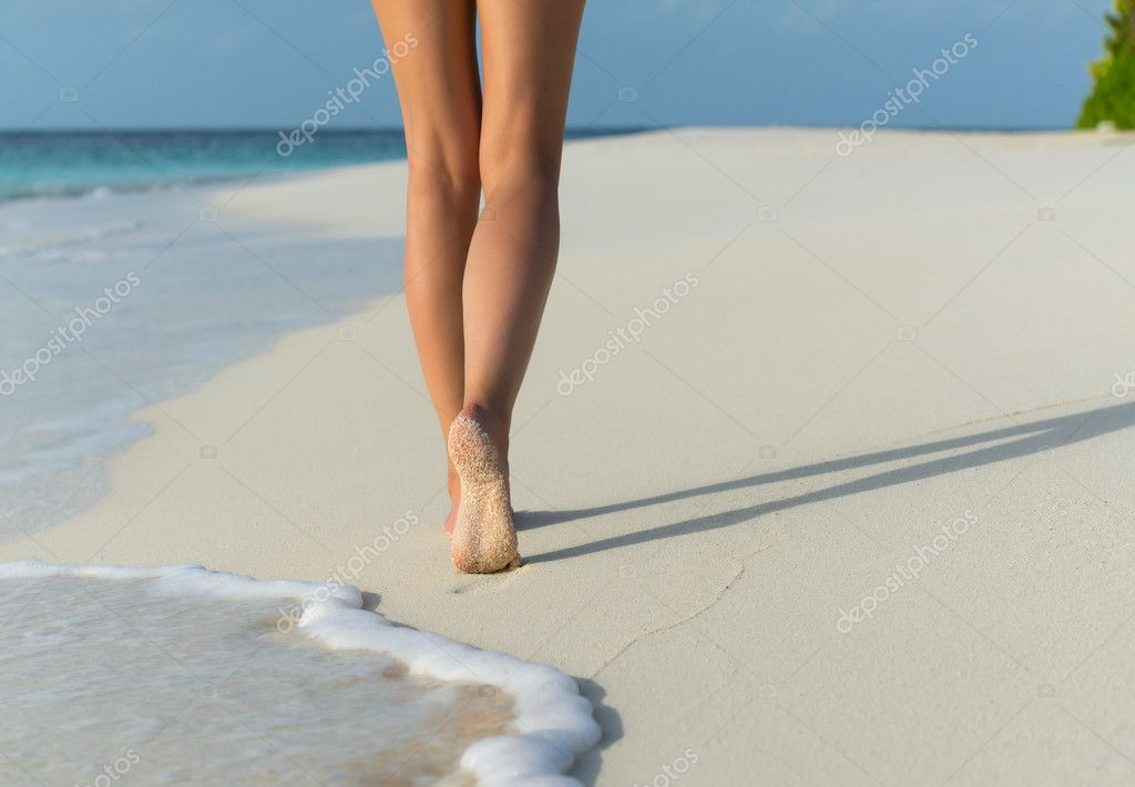 Beach travel - woman walking on sand beach leaving footprints in the sand. Closeup detail of female feet