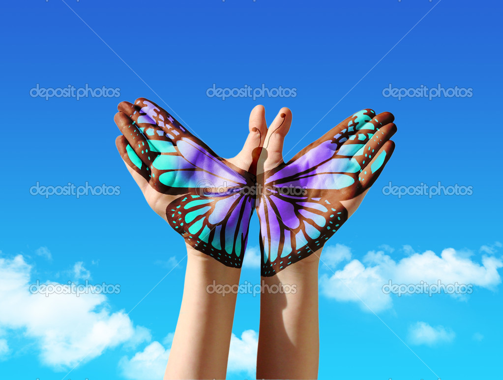 Uncategorized Butterfly Hand hand and butterfly painting tattoo over a blue sky stock photo