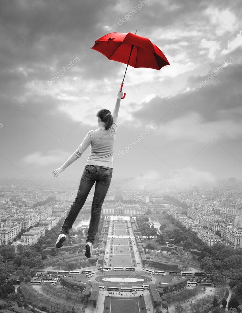 Young woman with red umbrella flying over Paris