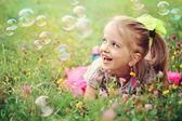 Fotografie glückliches kleines Mädchen spielen mit Blasen