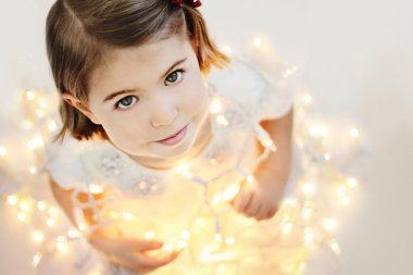 Cute, smiling little girl with glowing Christmas lights