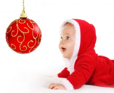 Christmas baby looking at a red ball