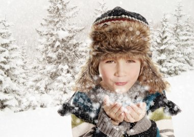 Happy boy blowing snowflakes in winter landscape