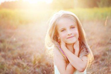 Happy little girl on summer meadow