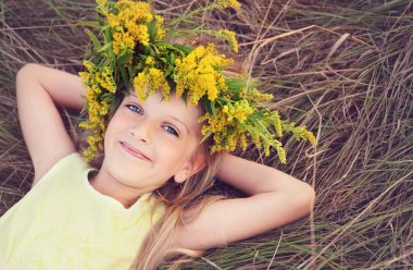 Happy little girl in flowers crown laying on the grass